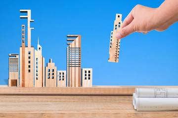 Hand holding miniature building, Real estate concept