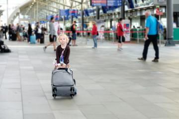 Kleines Mädchen mit koffer im flughafen