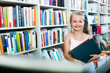 Small  girl standing in book store and taking  literature