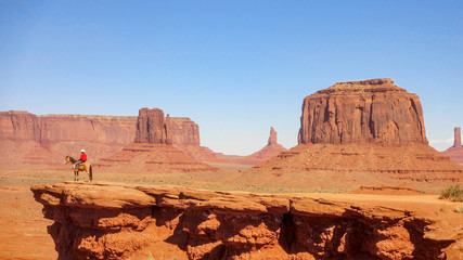 Monument Valley and a single horse rider at the end of the track at the edge of the steep cliff.