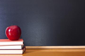Obraz books with apple and pen on the desk - fototapety do salonu