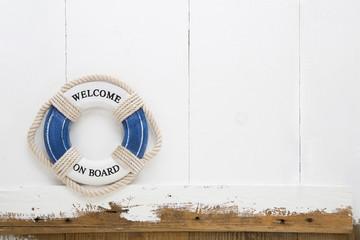 Welcome on board. Maritimer weißer Holz Hintergrund mit Rettungsreifen für Konzepte