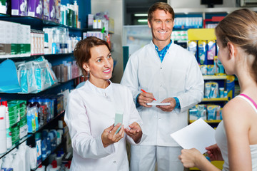 Smiling male and female pharmacists wearing white coats working