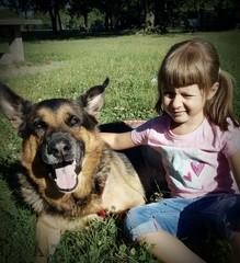 Bambina con cane pastore tedesco al parco