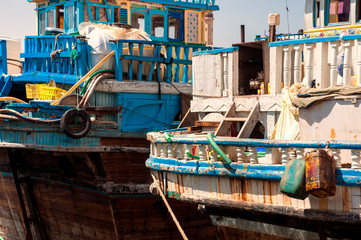 Traditional wooden dhows (boats) in Dubai creek district dock during busy trading day with sunny blue sky, Deira, United Arab Emirates
