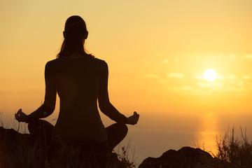 Woman meditating in a beautiful outdoor setting.