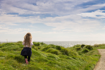 young girl with long blonde hair happily running along a coastal path on a beautiful sunny day.