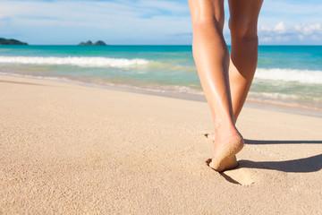 Woman walking on a white sand beach.