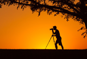 Male photographer taking photos of a beautiful sunset.