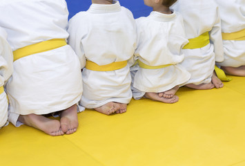 Foto op Aluminium Vechtsport Group of children in kimono sitting on tatami on martial arts training seminar. Selective focus