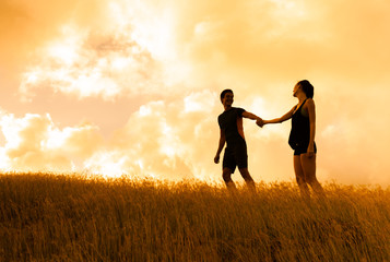 Young couple walking outdoors in the sunset.
