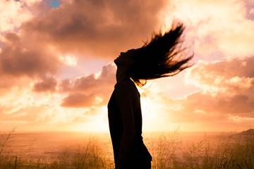 Happy and free woman enjoying the beautiful sunset.