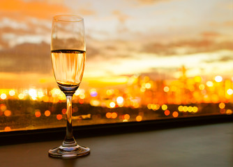 Wall Mural - Glass of champaign against a beautiful sunset in the city.