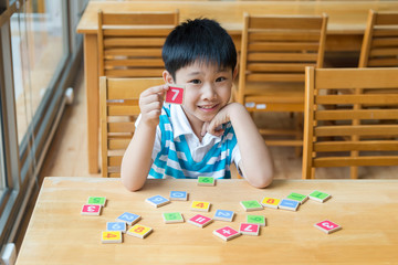Asian Boy With Wooden Toy Plate Numbers On Wood Table ,He Show plate Numbers In His Hand.