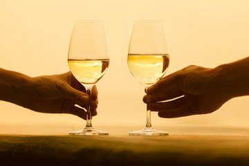 Closeup of man and woman holding glass of wine in a sunset setting.