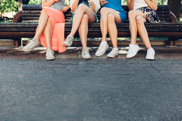 Girls sitting on a park bench with copy space