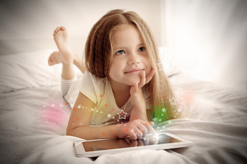 Cute little girl playing with tablet on white bed