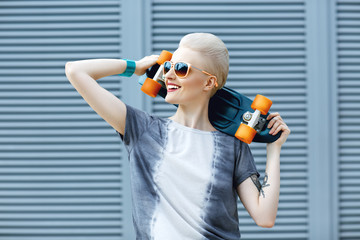 Young woman with short blonde hair smiling on the fashion background and holding little penny skateboard behind her head and looking awawy . The girl in joyful feelings. Outdoors, lifestyle.