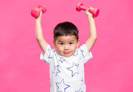 Little boy raising up dumbbells