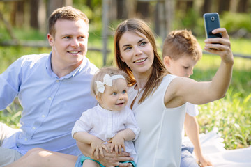 Happy family taking selfie with smartphone in park near forest
