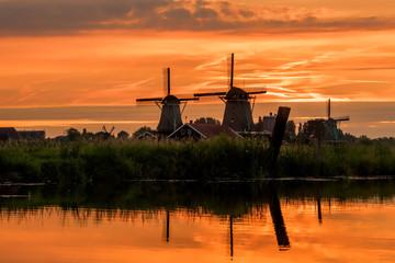 Türaufkleber Blumenhändler zonsondergang met molens en water