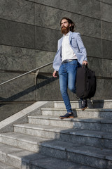 Stylish businessman walking with suitcase on stairs outdoors