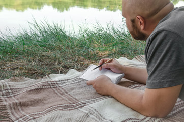 Man writing in his notebook in forest.