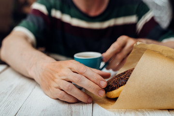 Man hands eating chocolate donut with coffee on wooden table