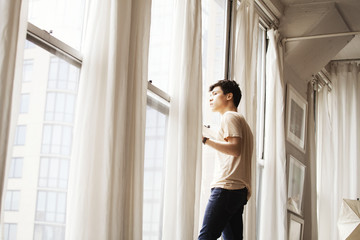 Young man looking through window
