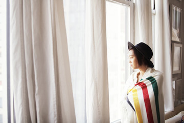 Thoughtful woman wrapped in blanket looking through window at home