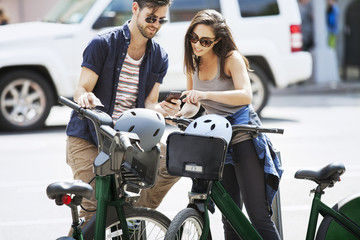 Couple using smart phone while standing with Citi Bikes on street