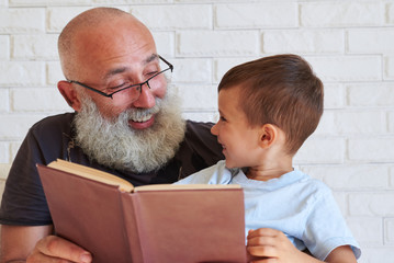 Close-up of aged man and small boy with a book looking at each o