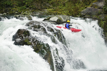 Kayaker paddling through waterfall in forest