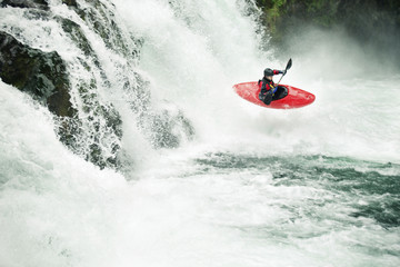 Whitewater kayaker paddling through river in forest