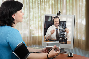 Woman measures blood pressure in front of virtual doctor