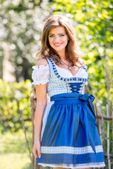 Beautiful young woman in traditional bavarian dress in park
