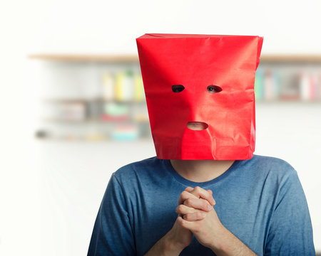 Portrait of shy guy in red paper bag over head