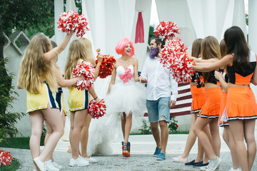 wedding couple with cheerleaders