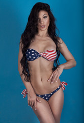Sexy woman in swimsuit with the USA flag colors and jeans shorts. Girl with perfect slim body. Studio shot. Long curly hair.