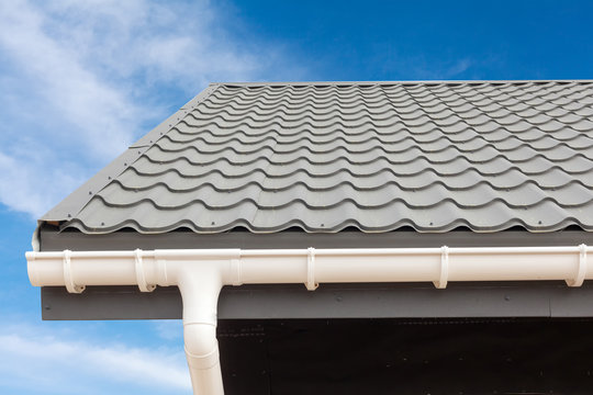 SIP panel house construction. New gray metal tile roof with white rain gutter