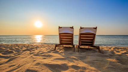 Two lounge chairs on tropical beach