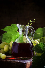Wine vinegar in a glass jug, dark vintage wooden background, sel
