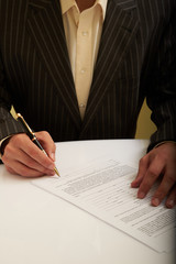 businessman in a suit signs the document