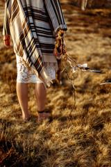 woman legs in native indian american boho dress walking in windy