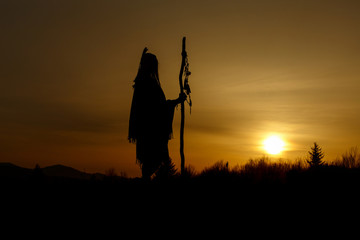 silhouette of native american shaman with pikestaff on backgroun