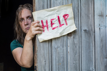 """A girl stands in front of the open door, and holding a piece of paper with the word """"help"""""""