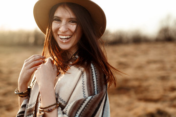 beautiful boho woman hipster, smiling, wearing hat and poncho at sunset in mountains, true emotions, space for text