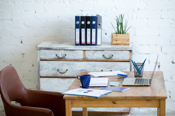 Home office interior in loft space with white brick walls. Cozy workplace with wooden table, office supplies, documents, notebook and laptop, leather chair and vintage wooden painted chest of drawers