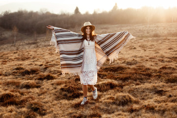 beautiful boho woman hipster having fun and dancing at sunset in