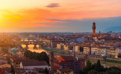 Sunset view of Ponte Vecchio over Arno River and Palazzo Vecchio in Florence, Italy